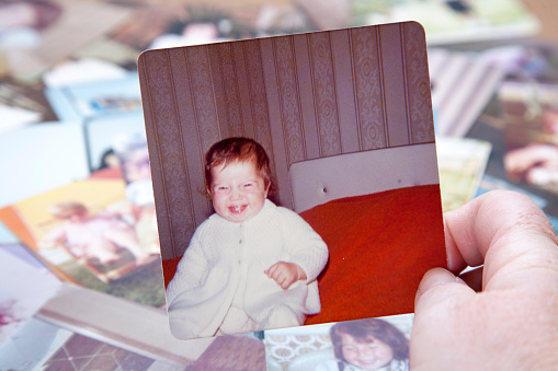 A baby photo taken in 1974 held in hand with more photographs in background. Same model in all photos.