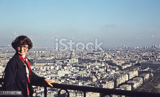 Vintage 1975 analog image of a young woman in a blue coat and red scarf enjoying the view and posing on the Eiffel tower with Paris in the background.