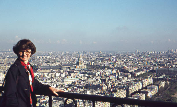 vintage 1975 analog image of a young woman in a blue coat and red scarf enjoying the view and posing on the eiffel tower with paris in the background. - viagens anos 70 imagens e fotografias de stock