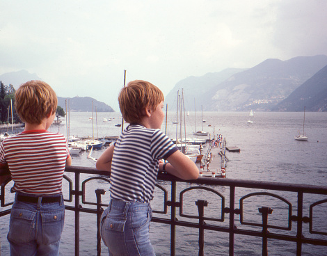 Vintage 1982 omage of two young boys both wearing jeans shorts and striped t-shirts overlooking lake Geneva in Switzerland.