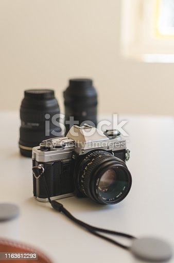 Vertical view of a vintage 35mm analogue camera surrounded with lenses and film on a table.  Analogue photography concep
