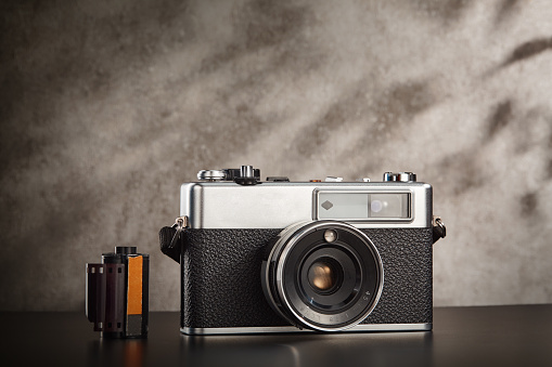 Vintage 35mm film camera with some shadows on the background wall