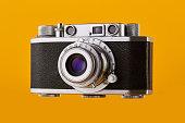 Vintage 35mm rangefinder film camera isolated on yellow / orange colored background