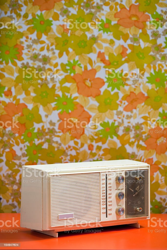 Vintage 60's 70's Clock Radio with floral wallpaper background orange stock photo