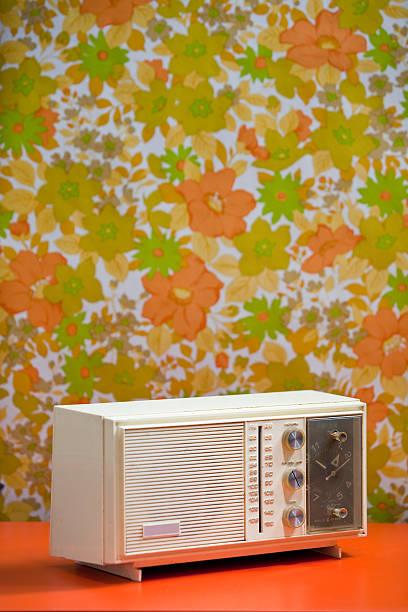 Vintage 60's 70's Clock Radio with floral wallpaper background orange stock photo