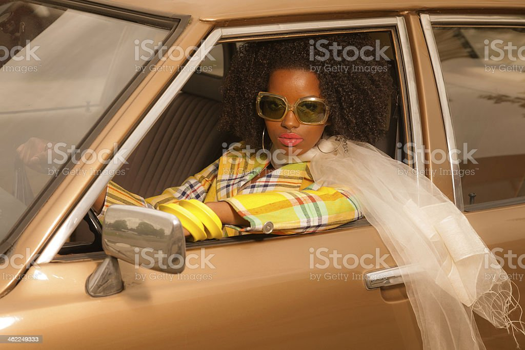 Vintage 70s fashion afro woman with sunglasses driving in car. stock photo