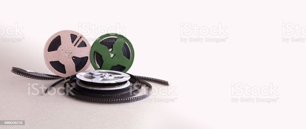 Vintage 8 mm cinema film reel. Retro design colorful celluloid accessories for home video projector. Beige background, selective focus copy space stock photo