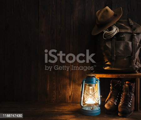Old fasioned nomad's gear in cozy dimmed atmospheric light of vintage gas lamp. Packed military backpack, rugged hiking boots, hat on wooden bench. Adventures are calling concept with copyspace.