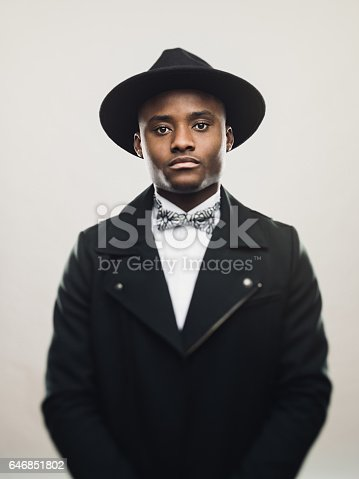 Portrait of vintage african american man wearing black suit and hat. Young male model looking at camera with serious expression against gray background. Vertical studio photography from a DSLR camera. Sharp focus on eyes.