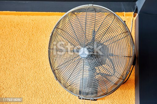 527550426istockphoto Vintage air cooling fan mounted on a yellow wall blowing air 1179318092