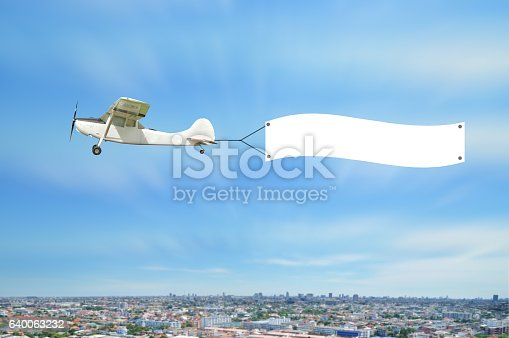istock Vintage airplane fly and show advertising board on sky 640063232