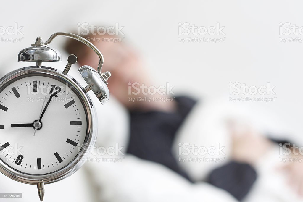 A vintage alarm clock and a blurred image of a man sleeping stock photo