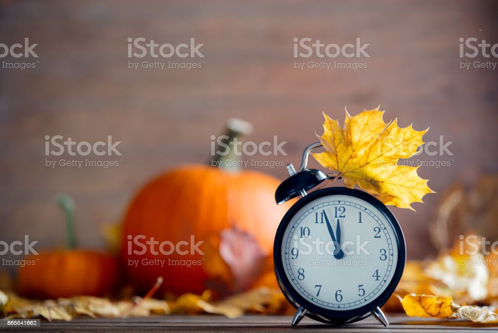 Vintage alarm clock and maple tree leaves with pumpkins stock photo