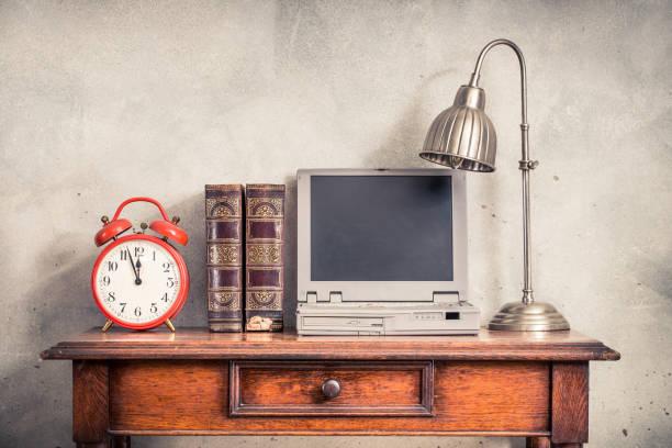 Oldtimer-Wecker, antike alte Bücher, veraltete tragbare Notebook-Computer aus den 90ern und Schreibtischlampe auf dem Eichenholztisch Beton Wand Hintergrund. Retro-Stil gefiltert Foto – Foto