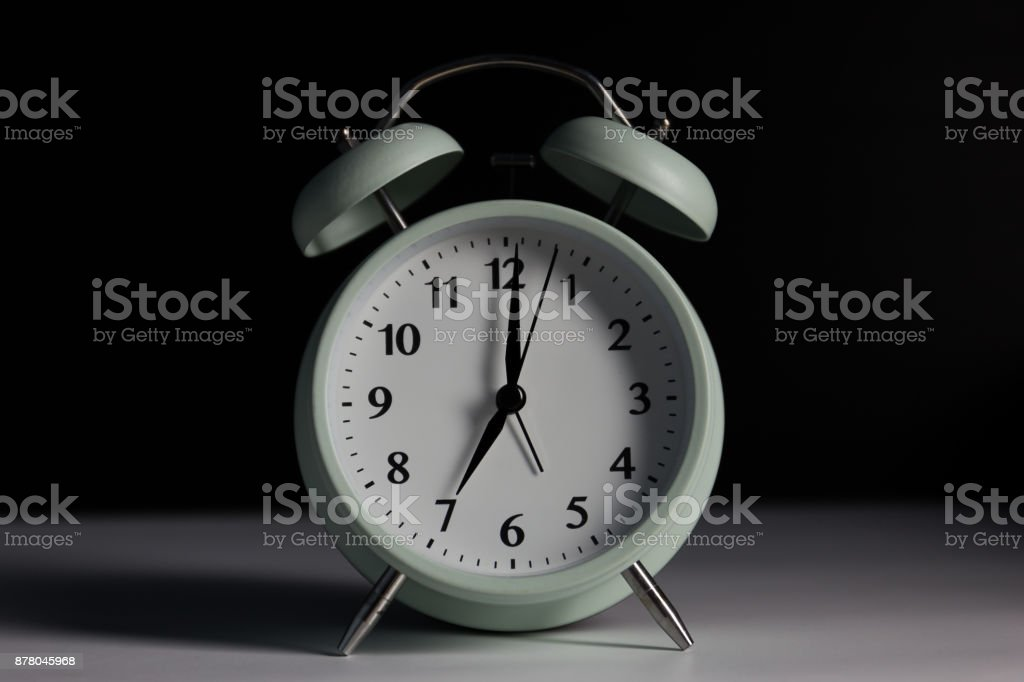 Vintage alarm clock in black background with light. stock photo