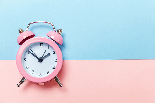1035679160 istock photo Vintage alarm clock Isolated on blue and pink pastel background 1134635249