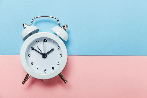 1035679160 istock photo Vintage alarm clock Isolated on blue and pink pastel background 1134635369