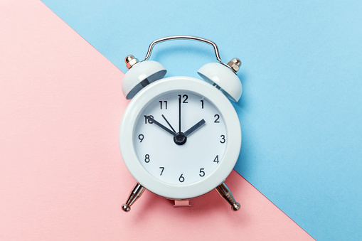 1035679160 istock photo Vintage alarm clock Isolated on blue and pink pastel background 1134635435