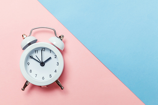 1035679160 istock photo Vintage alarm clock Isolated on blue and pink pastel background 1134635485