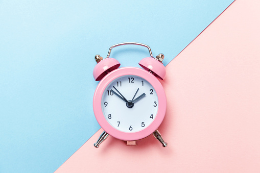 1035679160 istock photo Vintage alarm clock Isolated on blue and pink pastel background 1134635546