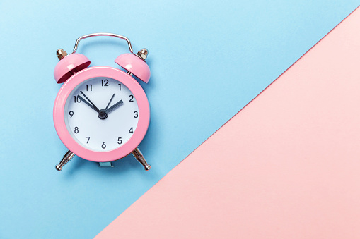 1035679160 istock photo Vintage alarm clock Isolated on blue and pink pastel background 1134635592