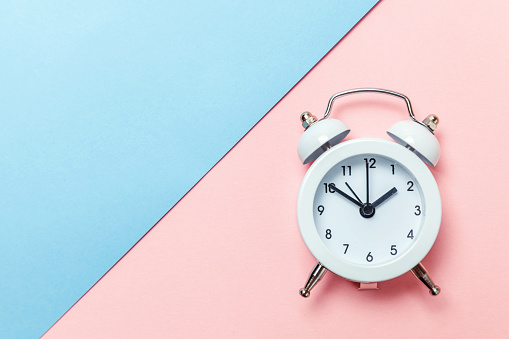 1035679160 istock photo Vintage alarm clock Isolated on blue and pink pastel background 1134635651