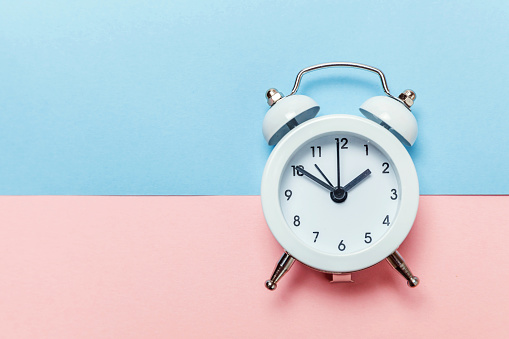 1035679160 istock photo Vintage alarm clock Isolated on blue and pink pastel background 1136902134