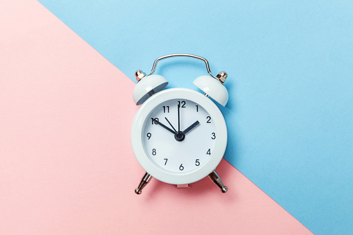 1035679160 istock photo Vintage alarm clock Isolated on blue and pink pastel background 1136902139