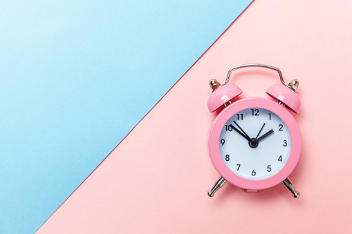 1035679160 istock photo Vintage alarm clock Isolated on blue and pink pastel background 1136902149
