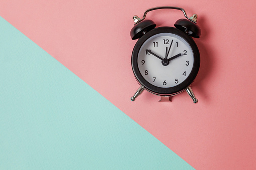 1035679160 istock photo Vintage alarm clock Isolated on blue and pink pastel background 1152881807