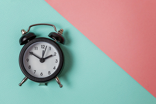 1035679160 istock photo Vintage alarm clock Isolated on blue and pink pastel background 1152881828