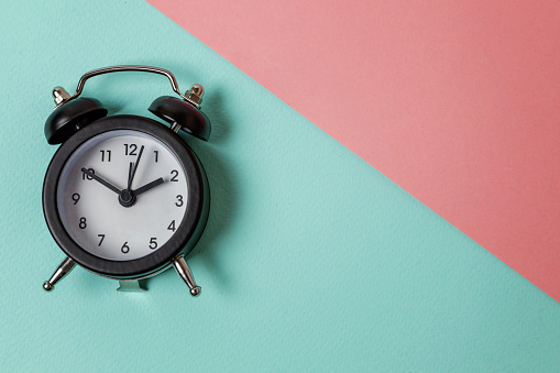 1035679160 istock photo Vintage alarm clock Isolated on blue and pink pastel background 1152881851
