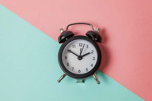 1035679160 istock photo Vintage alarm clock Isolated on blue and pink pastel background 1152882004