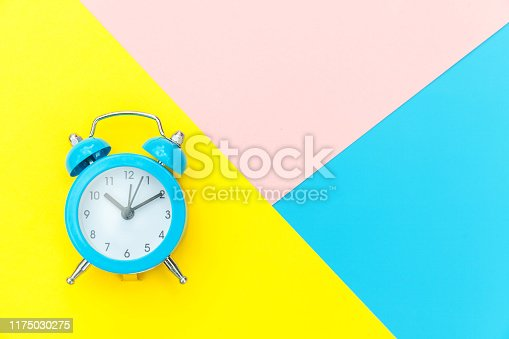 1139289535 istock photo Vintage alarm clock isolated on blue yellow pink pastel colorful trendy geometric background 1175030275