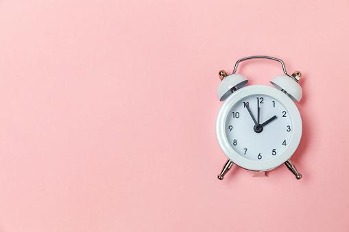 1035679160 istock photo Vintage alarm clock Isolated on pink pastel background 1136901951