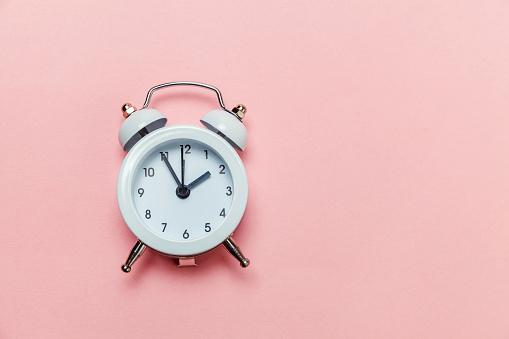 1035679160 istock photo Vintage alarm clock Isolated on pink pastel background 1136901961