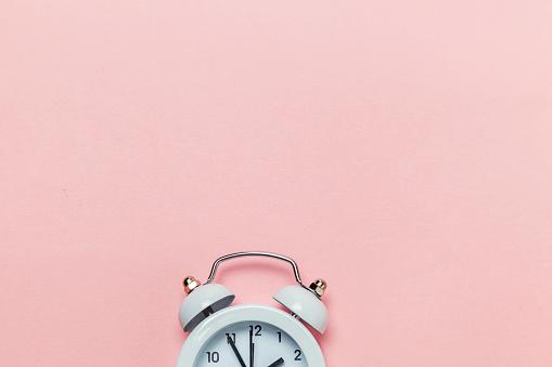 1035679160 istock photo Vintage alarm clock Isolated on pink pastel background 1136901980