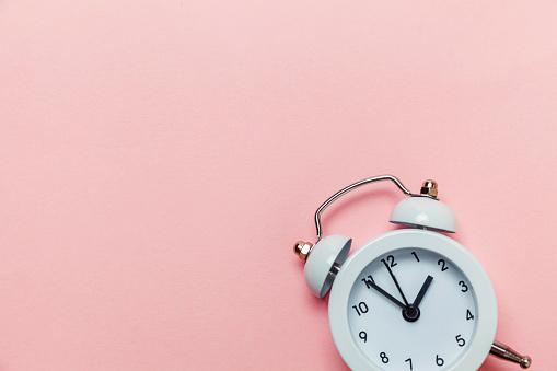 1035679160 istock photo Vintage alarm clock Isolated on pink pastel background 1136902021
