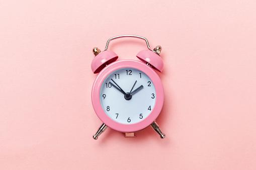 1035679160 istock photo Vintage alarm clock Isolated on pink pastel background 1136902087