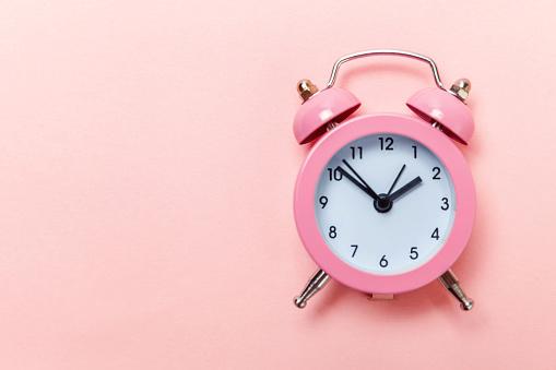 1035679160 istock photo Vintage alarm clock Isolated on pink pastel background 1136902092