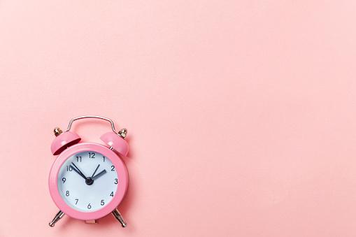 1035679160 istock photo Vintage alarm clock Isolated on pink pastel background 1136902099