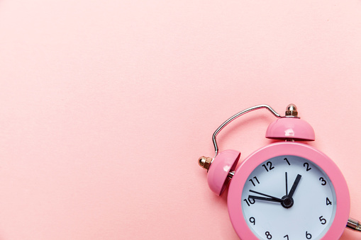 1035679160 istock photo Vintage alarm clock Isolated on pink pastel background 1136902105