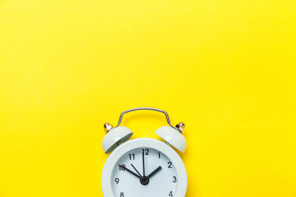 Vintage alarm clock Isolated on yellow background Ringing twin bell vintage classic alarm clock Isolated on yellow colourful trendy modern background. Rest hours time of life good morning night wake up awake concept. Flat lay top view copy space countdown stock pictures, royalty-free photos & images