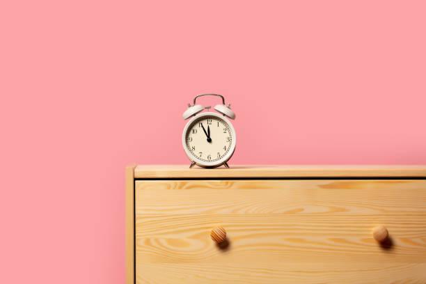 vintage alarm clock on bedside table stock photo