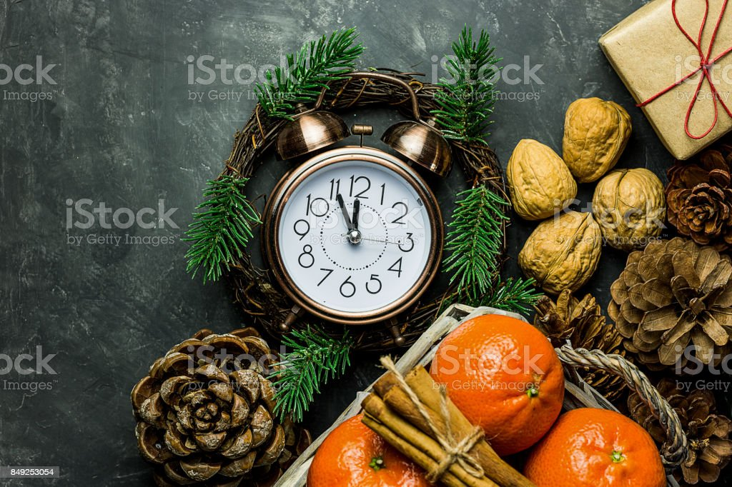 Vintage alarm clock set to five minuted to midnight. New Year's eve countdown. Pince cones walnuts tangerines cinnamon sticks gift box in craft paper. Christmas greeting card poster. Copy space stock photo