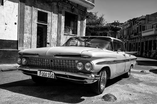 Havana, Сuba - April 19, 2016: Vintage American car, 1959 Chevrolet Impala 4 Door Hard Top Sport Sedan, parked on the street next to colonial buildings in Old Havana, Cuba
