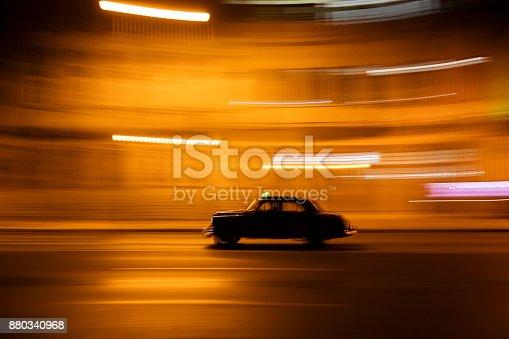 Motion blurred vintage American car goes down the street at night in Havana, Cuba