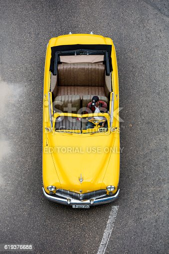 Havana, Сuba - April 20, 2016: Vintage, yellow American convertible car, 1950 Mercury Eight, driving down the street in Havana Vieja, Cuba, elevated view.