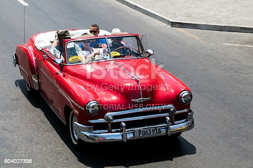Havana, Сuba - April 13, 2016: Vintage red American car, 1952 Chevrolet Styleline Deluxe Convertible, with tourists, driving down the street in Havana, Cuba, elevated view