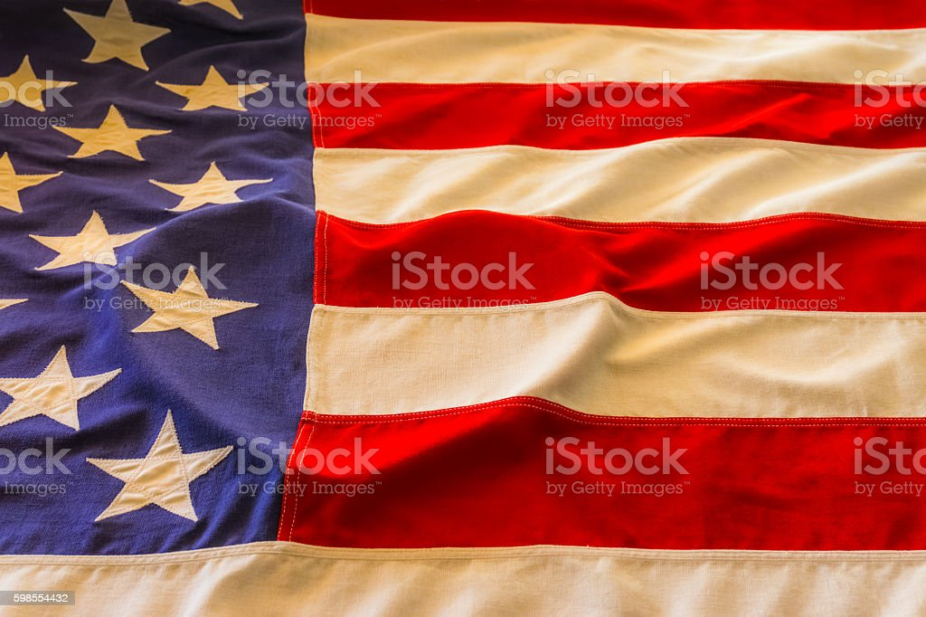A vintage American flag lays with a heart shape raised in it...
